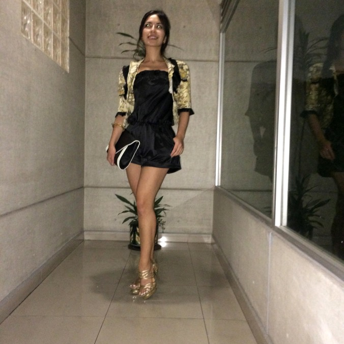 Outfit: black playsuit with a small jacket and high golden heels.